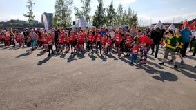 Energiczni dzieciaki tanczy dla wydarzenia jest ubranym czerwonego jercey w s?onecznym dniu zbiory