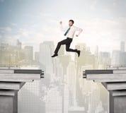 Energiczny biznesowy mężczyzna skacze nad mostem z przerwą fotografia stock