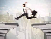 Energiczny biznesowy mężczyzna skacze nad mostem z przerwą zdjęcie stock