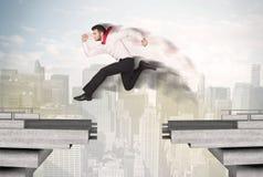 Energiczny biznesowy mężczyzna skacze nad mostem z przerwą obrazy royalty free