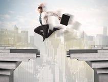 Energiczny biznesowy mężczyzna skacze nad mostem z przerwą zdjęcia royalty free