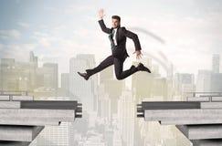 Energiczny biznesowy mężczyzna skacze nad mostem z przerwą obraz royalty free