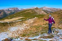 Energiczny Żeński wycieczkowicza odprowadzenie na Śnieżnym i Trawiasty ślad w Scenicznym Mountain View i zdjęcie royalty free