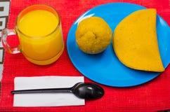 Energiczny i zupełny śniadanie zawiera sok pomarańczowego, empanada i bolon słuzyć na błękitnym talerzu z czarną łyżką, obrazy stock