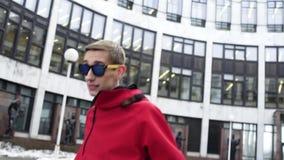 Energiczny mężczyzna w czerwonym sporcie odzieżowym i okularach przeciwsłonecznych tanczy obok granitowych kolumn zbiory
