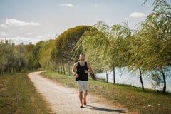 Energiczny młody człowiek ćwiczenia outdoors utrzymuje ich parku w obrazy stock