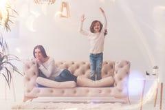 Energiczny niemądry dzieciak skacze up na kanapie zdjęcie royalty free