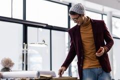 Energiczny przyjemny fashionably będący ubranym kierownik patrzeje biurowego biurko zdjęcia stock