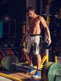 Energiczny silnego mężczyzny podnośny barbell w crossfit gym na ciemnym sporta klubu tle niska sekcja obrazy stock