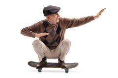Energiczny starszy mężczyzna jedzie deskorolka zdjęcia royalty free