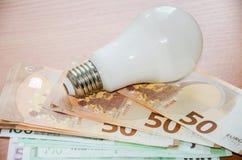 Energie - besparing lightbulb, euro op een houten lijst stock fotografie