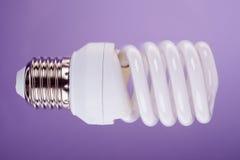 Energie - besparings gloeilamp op blauwe close-upachtergrond Stock Foto