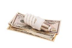 Energie - besparingsconcept door gloeilamp wordt op dollar wordt geplaatst vertegenwoordigd die stock foto