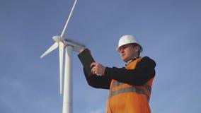 Energie-Ingenieur der Windmühle, zum mit der Tablette bei Sonnenuntergang zu arbeiten umwelt stock video footage