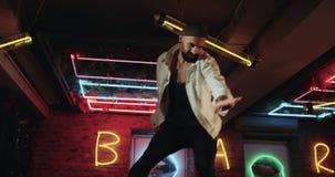 Energie- junge Männer mit dem tanzenden Überraschen des Bartes in der Stange mit erstaunlichen Lichtern auf dem Hintergrund stock video