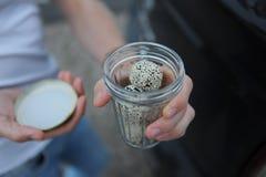 Energiebonbons von den Trockenfrüchten besprüht mit Samen des indischen Sesams in einem facettierten Glas in einer Mann ` s Hand stockbilder