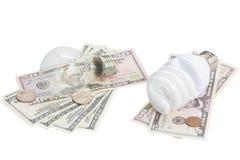 Energieeinsparung und Normal   Birnen auf Dollargeld Lizenzfreie Stockfotos