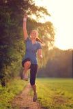 Energiefrau, die in die Luft springt Stockfotografie