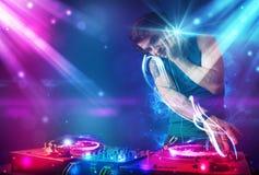 Energiek DJ die muziek mengen met krachtige lichteffecten Stock Foto