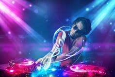 Energiek DJ die muziek mengen met krachtige lichteffecten Royalty-vrije Stock Afbeeldingen