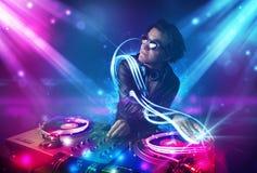 Energiek DJ die muziek mengen met krachtige lichteffecten Stock Afbeeldingen