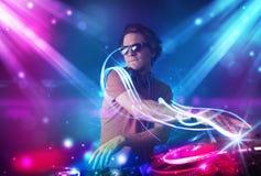 Energiek DJ die muziek mengen met krachtige lichteffecten Royalty-vrije Stock Foto