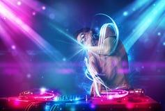Energiek DJ die muziek mengen met krachtige lichteffecten Royalty-vrije Stock Fotografie