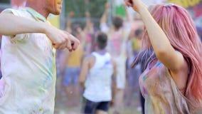 Energiek jong paar omvat in gekleurd poeder die aan muziek en het glimlachen dansen stock video