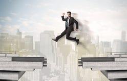 Energieke bedrijfsmens die over een brug met hiaat springen royalty-vrije stock fotografie