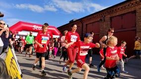 Energieke jonge geitjes die marathon van een beginnend teken voor een gebeurtenis in werking stellen die rode jercey dragen stock video
