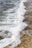 Energieke overzeese golven die op de kade rollen Stock Foto's