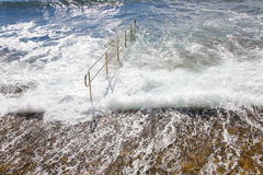 Energieke overzeese golven die op de kade rollen Stock Foto