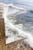 Energieke overzeese golven die op de kade rollen Stock Afbeelding