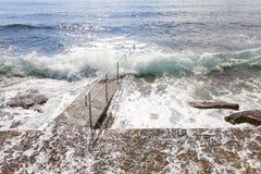 Energieke overzeese golven die op de kade rollen Royalty-vrije Stock Afbeeldingen
