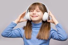 Energiekindermädchen mit Kopfhörern hörend Musik mit geschlossenen Augen auf weißem Hintergrund lizenzfreie stockfotos