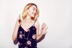 Energiemädchenkopfhörer, die Musik mit geschlossenen Augen auf Hintergrund im Studio hören Haar im Endstück fliegt vom Bewegen Stockfotos
