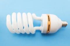 Energiesparende Glühlampe auf einem blauen Hintergrund Stockbild