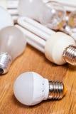 Energiesparende LED-Lampe und Stapel von alten Birnen Stockfoto