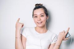 Energiflicka med hörlurar som lyssnar till musik med stängda ögon Hon bär den vita T-tröja royaltyfri fotografi