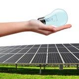 Energii słonecznej żarówka w ręce i panel Fotografia Royalty Free