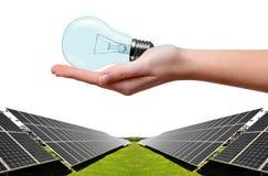 Energii słonecznej żarówka w ręce i panel Obrazy Stock
