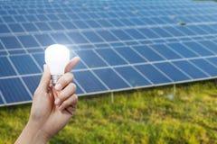 Energii słonecznej żarówka w ręce i panel, energia Zdjęcia Royalty Free