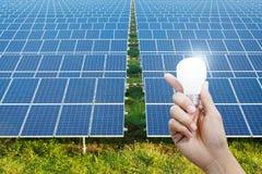 Energii słonecznej żarówka w ręce i panel, energia Fotografia Royalty Free