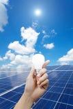 Energii słonecznej żarówka w ręce i panel, energia Zdjęcia Stock