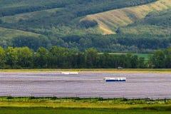 Energii słonecznej roślina na tle zieleni wzgórza Obraz Stock