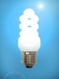 Energiräddninglampa på en blå bakgrund. Arkivfoton
