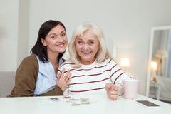 Energische ältere Frau und Pflegekraft, die Puzzlespiel aufhebt stockbilder