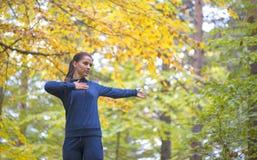 Energische junge Frau tun Übungen draußen im Park, um ihre Körper in Form zu halten stockbild