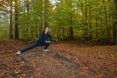 Energische junge Frau tun Übungen draußen im Park, um thei zu halten lizenzfreies stockbild