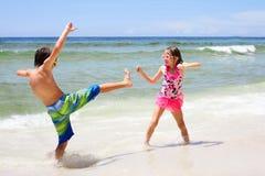 Energische kleine Kinder, die auf Strand in Meer kämpfen Stockbild